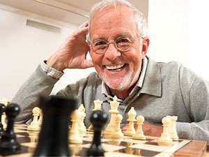 portrait of haapy elderly man playing chess