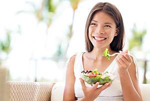 photo of happy woman holding a bowl of fresh salad